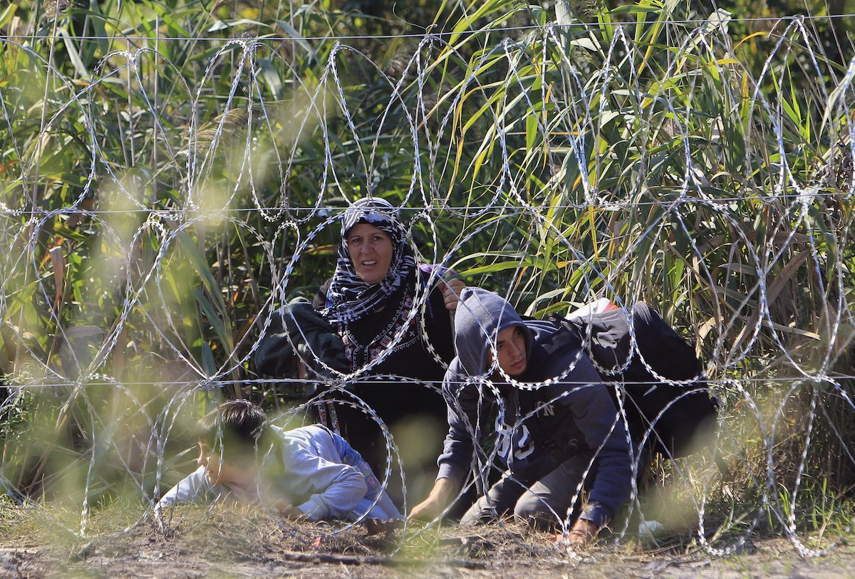 A Syrian migrant family, on the Serbian side of the border with Hungary, looks out from behind a wire fence, near Roszke