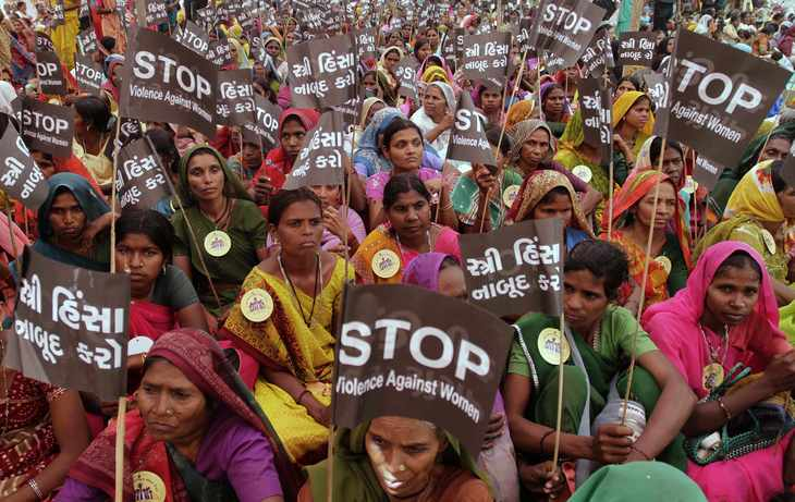 Women hold placards as they take part in a rally to mark the International Women's Day in Ahmadabad, India, Monday, March 8, 2010. India's government introduced a bill to parliament on Monday that proposes to reserve one-third of the legislature's seats for women, angering socialist lawmakers who tore up papers and tried to tear out microphones. (AP Photo/Ajit Solanki)