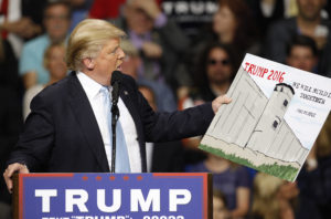 U.S. Republican presidential candidate Donald Trump holds a sign supporting his plan to build a wall between the United States and Mexico that he borrowed from a member of the audience at his campaign rally in Fayetteville, North Carolina March 9, 2016. Trump was interrupted repeatedly by demonstrators during his rally. REUTERS/Jonathan Drake - RTSA418