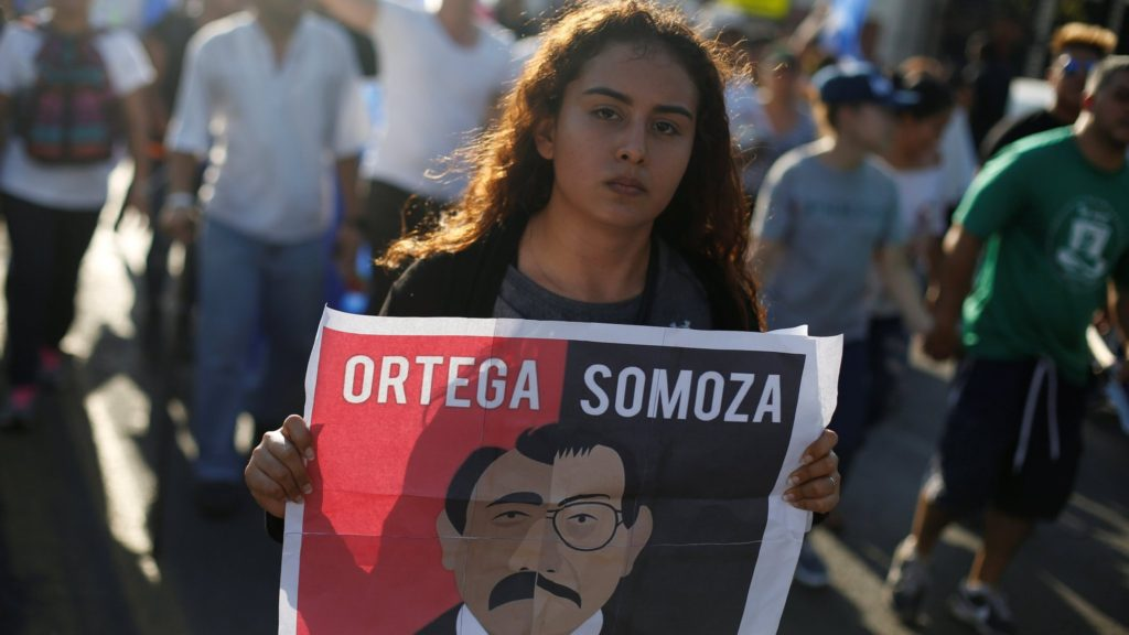 A demonstrator holds a sign showing Nicaraguan President Daniel Ortega and former President Anastasio Somoza during a protest against police violence and the government of President Ortega in Managua, Nicaragua April 23, 2018. REUTERS/Jorge Cabrera